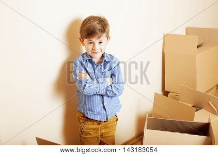 little cute boy in empty room, remove to new house. home alone among boxes close up kid