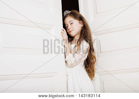 little cute girl at home, opening door well-dressed in white dress and tiara