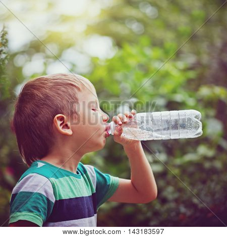 Little boy drinking mineral water from the plastic bottle on outdoor. Toning image