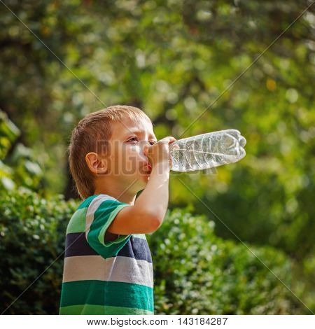 Cute little boy drinking mineral water from the plastic bottle in the park