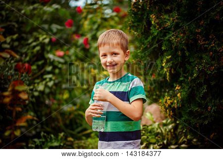 Sweet little boy drinking mineral water from the plastic bottle outdoor