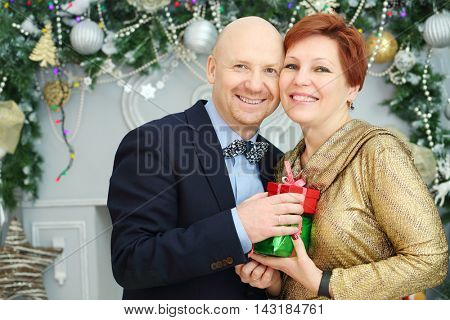 Happy husband and wife hold gifts in room with christmas decoration