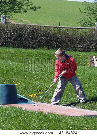 Little boy trying to play golf on vacation