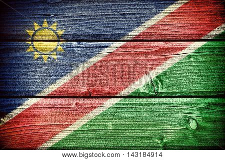 flag of Namibia painted on old grungy wooden background: 3d illustration