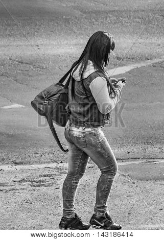 MONTEVIDEO, URUGUAY, NOVEMBER - 2015 - Black and white urban scene of young woman carelessly watching his cellphone on the street of Montevideo Uruguay