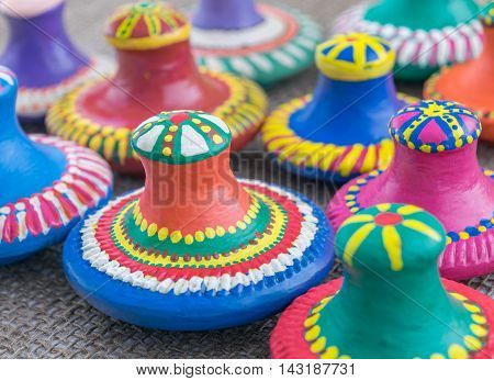 Angled view showing a still life of colorful painted pottery lids on sackcloth background