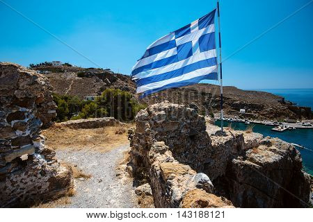 Greek flag on hill with ancient ruins near Chora Sfakion town on Crete island, Greece