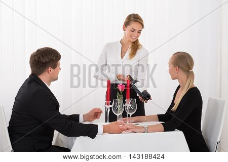 Young Waitress Suggesting Bottle Of Red Wine To Couple In Restaurant