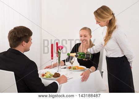 Female Waitress Pouring Champagne Into Glass For Happy Young Couple In Restaurant
