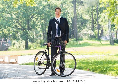 Portrait Of Male Businessman Standing With His Bicycle At Park