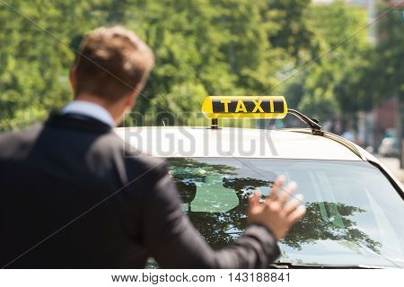Close-up Photo Of A Businessman Calling Taxi