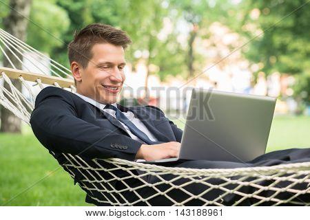 Happy Young Man Lying In Hammock Using Laptop