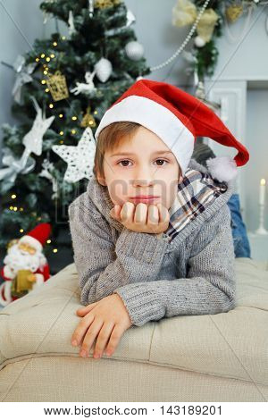 Handsome boy in red santa cap lies on couch near Christmas tree