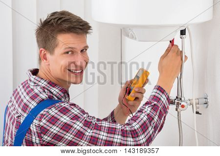 Smiling Male Plumber Examining Electric Boiler With Multimeter Probe