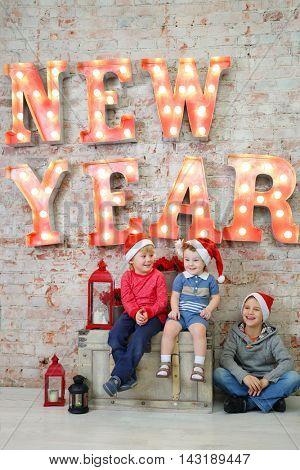 Three happy children in santa caps pose in studio with big trunk