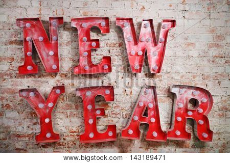 Big red letters with lamps - New Year - on brick wall indoor