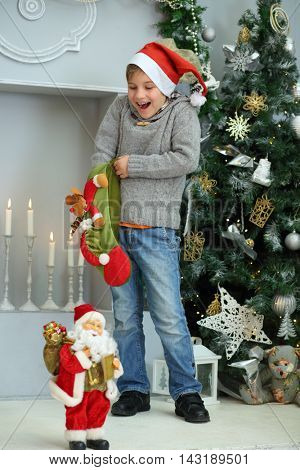 Happy boy in red santa cap takes out sock gift near christmas tree