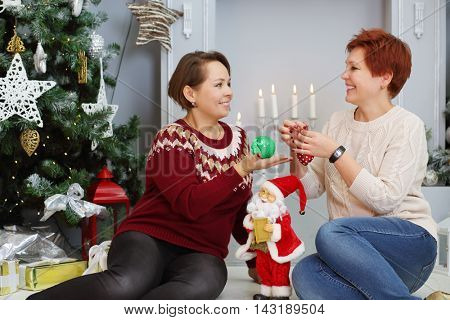Two happy middle-aged women sit on floor with balls near christmas tree