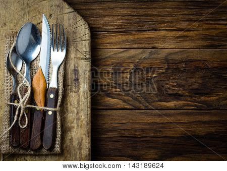 Autumn Halloween Thanksgiving composition. Autumn rustic set of cutlery knife, spoon, fork, tea spoon on rustic cutting board wtih autumn yellow leaves. Copy space, top view