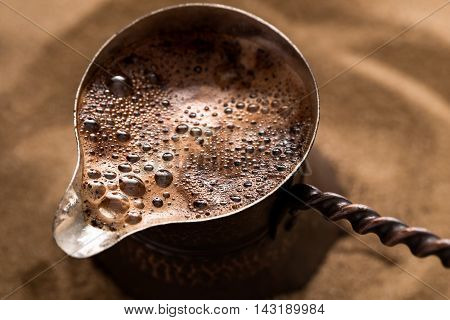 Coffee brewing in turkish pot in hot sand, cezve. Closeup shot, top view.