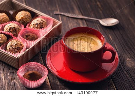 Coffee cup and truffles on wooden table