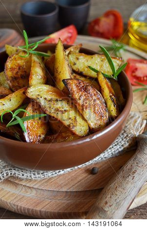 Baked potato wedges with rosemary and garlic on a wooden background