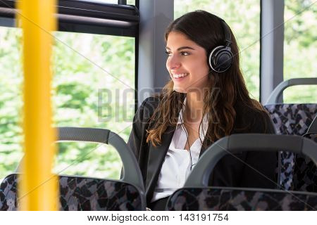 Happy Businesswoman Listening Music While Traveling By Bus