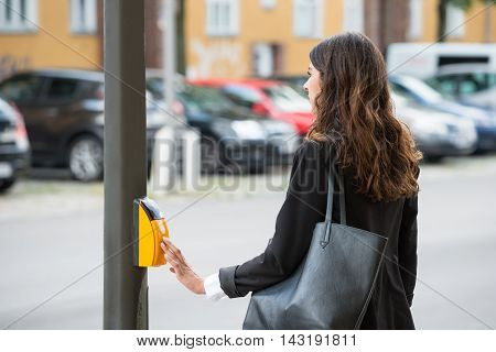 Young Businesswoman Pressing Yellow Crosswalk Button On Pedestrian Crossing