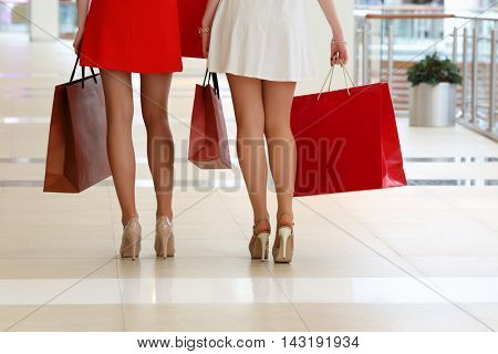 Legs of two girls in dresses standing with bags in shopping center