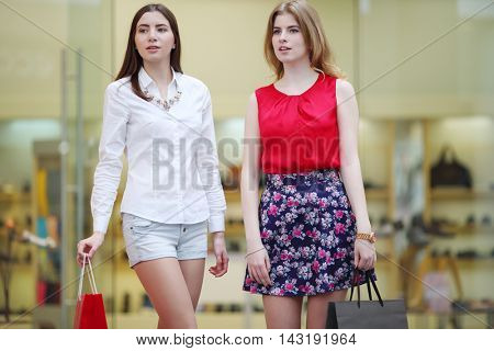 Two pretty girls with bags looks away in big modern mall, shallow dof