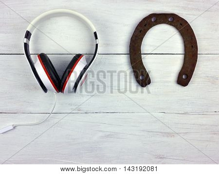 Everyone has their own hobbies.Headphones and horseshoe on wooden background. Top view. / Lines (forms) in stories. Joke. / Past and Present.Choose your passion.Travel with music. Toning.