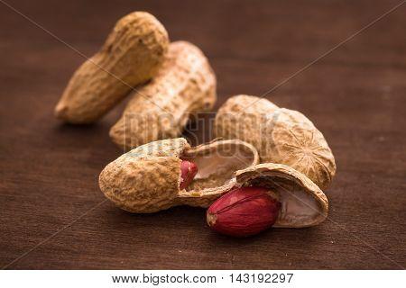 Few peanuts on dark background closeup shot