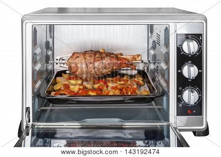 Leg of turkey baked with potatoes and tomatoes in an electric oven on skewer isolated on white background with clipping paths