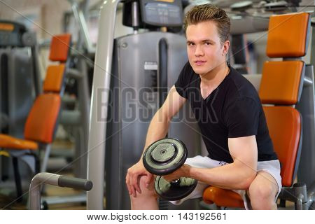 Young handsome man sits and raises dumbbell in left hand in fitness club