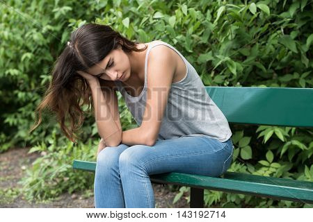Portrait Of A Sad Young Woman Sitting On Bench In Park