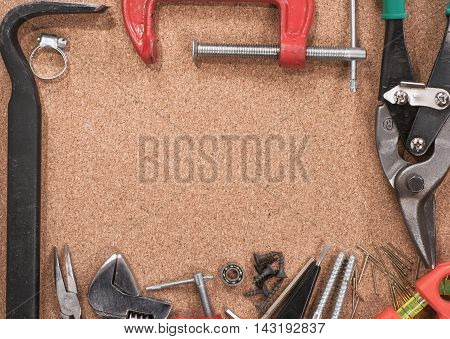 Frame of various tools on brown background