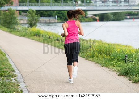 Rear View Of Sporty Young Woman Running On Path