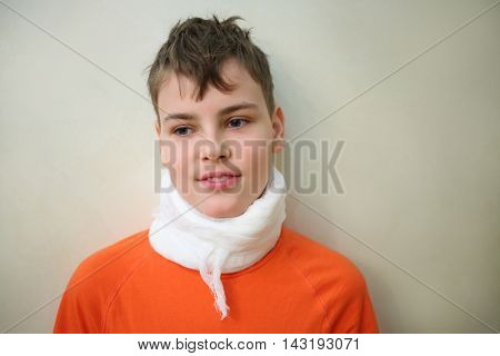 Closeup of smiling boy teenager with bandaged with gauze neck near wall