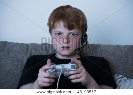 Portrait Of Boy With A Joystick Playing Videogames At Home