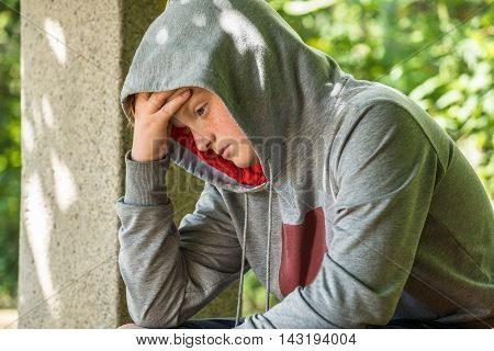 Unhappy Boy Wearing Grey Hoodie Sitting In Park