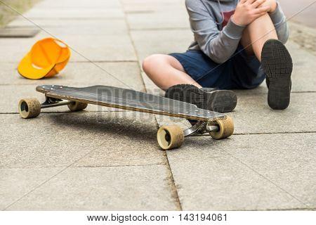 Boy With Knee Injury Sitting Near Skateboard On Sidewalk