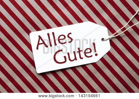 One Label On A Red And Brown Striped Wrapping Paper. Textured Background. Tag With Ribbon. German Text Alles Gute Means Best Wishes