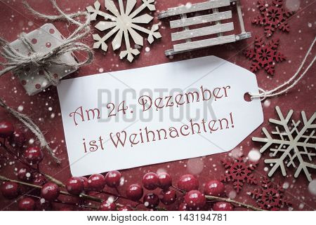 Nostalgic Christmas Decoration Like Gift Or Present, Sleigh. Card For Seasons Greetings With Red Paper Background. German Text Am 24. Dezember Ist Weihnachten Means Christmas