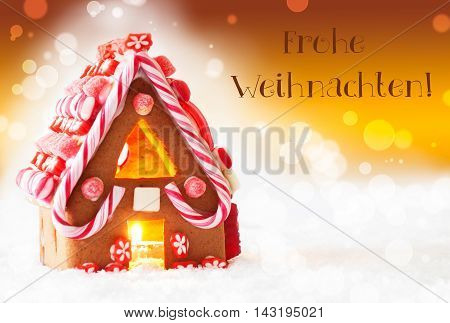 Gingerbread House In Snowy Scenery As Christmas Decoration. Candlelight For Romantic Atmosphere. Golden Background With Bokeh Effect. German Text Frohe Weihnachten Means Merry Christmas