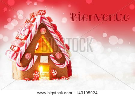 Gingerbread House In Snowy Scenery As Christmas Decoration. Candlelight For Romantic Atmosphere. Red Background With Bokeh Effect. French Text Bienvenue Means Welcome