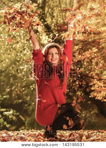 Woman Relaxing In Autumn Park Throwing Leaves Up In The Air
