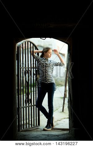 Young teen girl in fashionable shirt and jeans standing near forged dorr in arch