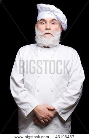 Bearded man cook in chef hat and uniform in studio on black background