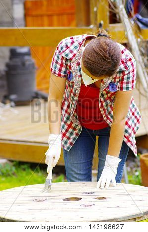 woman with handgloves painting a wood table.