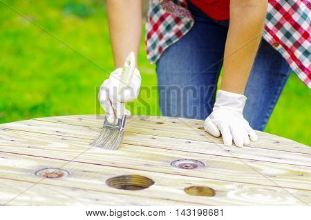 woman wearing gloves cleaning a wood table with a brush.